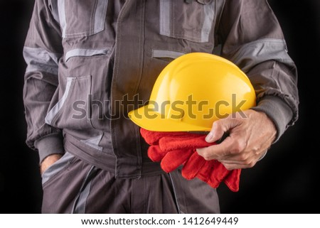 A production worker in workwear with a protective helmet in his hand. Special workwear for employees. Dark background.