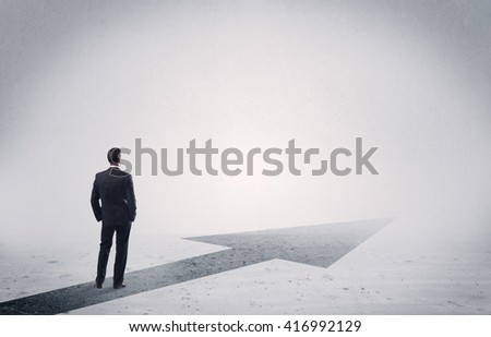 A professional businessman thinking while standing on a black arrow pointing forward in grey space concept #416992129