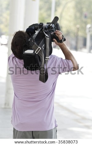 A Professional Cameraman Filming An Outdoor Scene
