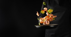 A professional chef cooks shrimp in a pan with brussels sprouts, vegetables. Cooking seafood, healthy vegetarian food and food on a dark background. Freezing in motion. Horizontal view. Banner.