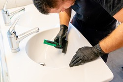 A professional cleaner removing dirt stains from a ceramic bathroom sink with a diamond blade scraper and cloth