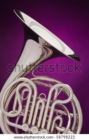 A professional double French horn isolated against a spotlight purple background.