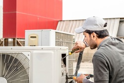 a professional electrician man is fixing a heavy duty unit of central air conditioning system by his tools on the roof top and wearing grey color of uniform and white cap