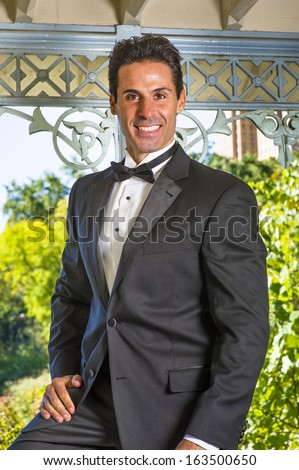 stock-photo-a-professional-executive-is-dressing-in-a-black-tuxedo-smilingly-looking-at-you-portrait-of-163500650.jpg