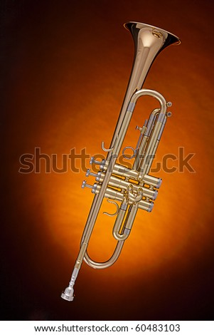A professional gold trumpet cornet isolated against a spotlight gold background.