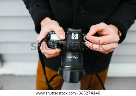 A professional photographer adjusts the camera before shooting, hands, camera, background #365274140