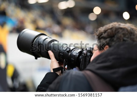 A professional photographer with a professional camera shoots a football match at the stadium