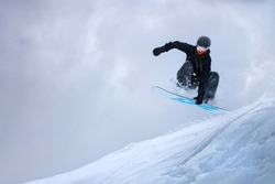 A professional snowboarder girl in flight after jumping from a snow eaves makes a rake against the gray sky on a cloudy day. The concept of winter sports freeride and freestyle
