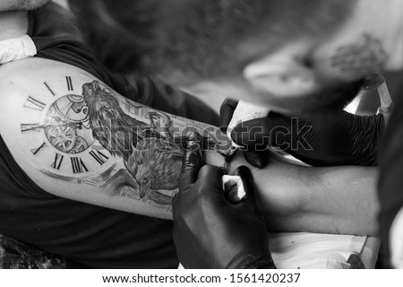 A professional tattoo artist introduces black ink into the skin using a needle from a tattoo machine. tattoo art on body..Professional tattooist working black and white tattooing in studio.