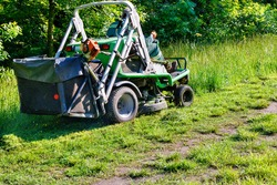 A professional tractor lawn mower mows tall grass along a park grove, climbing up the slope and managed by a utility worker, copy space.