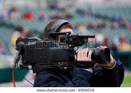 A professional videographer at a baseball game.