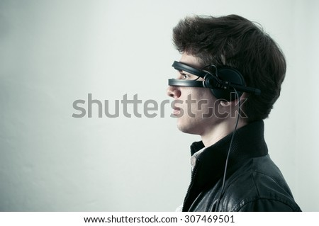 A profile portrait of a young man with a pair of headphones placed in a way to cover his eyes like a futuristic set of sunglasses