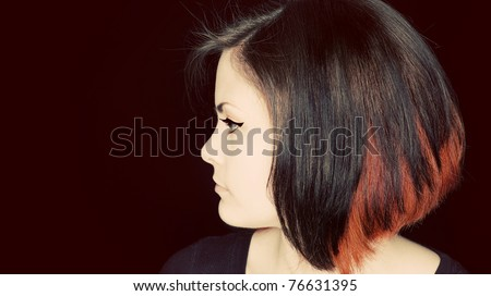 A profile portrait of a young woman with funky hair.