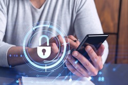 A programmer is browsing the Internet in smart phone to protect a cyber security from hacker attacks and save clients confidential data. Padlock Hologram icons over the typing hands.