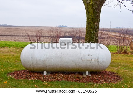 A propane fuel container sitting out near an open field.