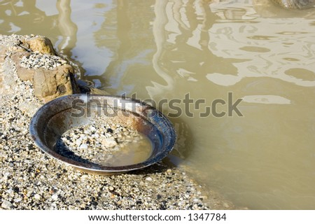 A prospector's pan left by the river. This is the pan that is used to search for alluvial gold in the stones of the river.