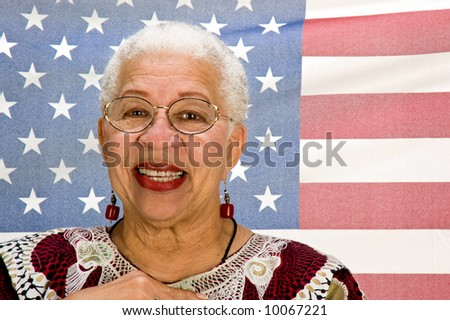 A proud African-American woman standing in front of a translucent American flag with her hand over her heart.