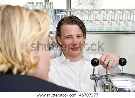 a proud bartender looking at a talking customer while leaning on the handles of his bar