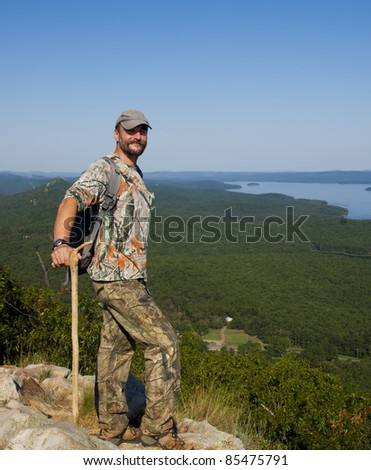 A proud man is with a backpack standing on top of a mountain and looking at the landscape with the river Arkansas