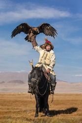 A proud young kazakh eagle hunter posing with his golden eagle on horseback on the backdrop of blue sky. Ulgii, Mongolia.