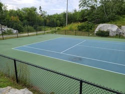 A public park with tennis courts that are gated in with a chain link fence. The courts are new and are a green color. They are surrounded by forest and open fields of grass.