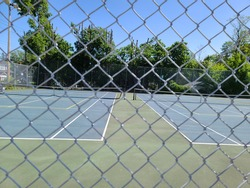 A public park with tennis courts that are gated in with a chain link fence. The courts have a reddish color floor and is surrounded by forest and open fields of grass.