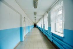 a public school, a long empty corridor with blue walls. The concept of quarantine