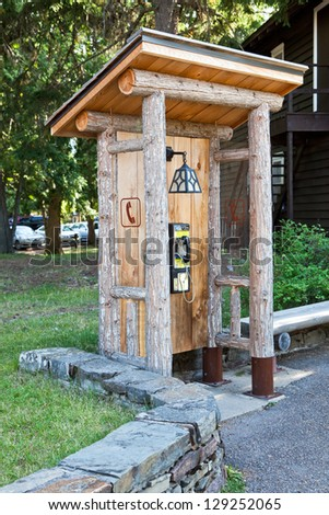 A public telephone booth made from logs and boards with a sloped roof and hanging lamp in Glacier National Park, Montana.