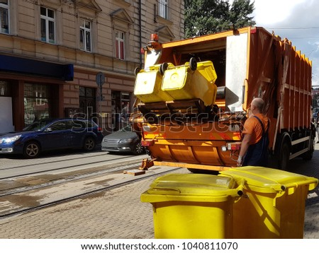 A public utility worker collects garbage from garbage cans in a garbage truck in the historic city. Ecology of city life. Waste management in the modern world. Prestigious and affordable work. #1040811070