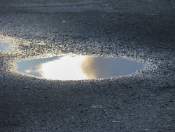 A puddle of water. The sun was intercepted from the eyes by cloud.