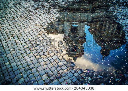 A puddle reflection of the basilica of St Agnes on Piazza Navona in Rome, Italy, covered with colorful confetti after the carnival parade #284343038