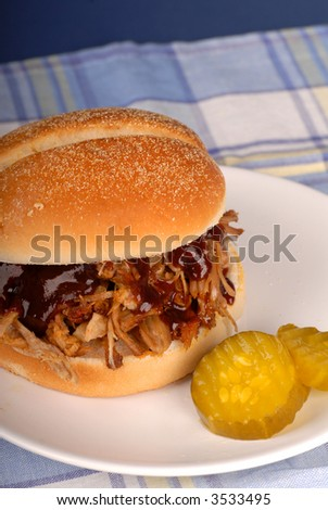 A pulled pork sandwich with pickles on a white plate