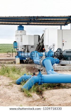 A pumping station where water is pumped from a ground well, and distributed to multiple agricultural sprinklers systems in the fertile farm fields of Idaho. #1339718330