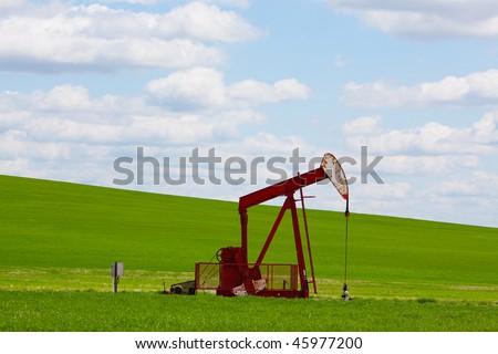 A pumpjack by a grassy hill. Alberta, Canada.