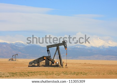 A Pumpjack pumping oil from an oil well in the plains with snow capped mountains in the backgroud.