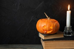 A pumpkin and a candle stand on old books. Dark background. Copy space.