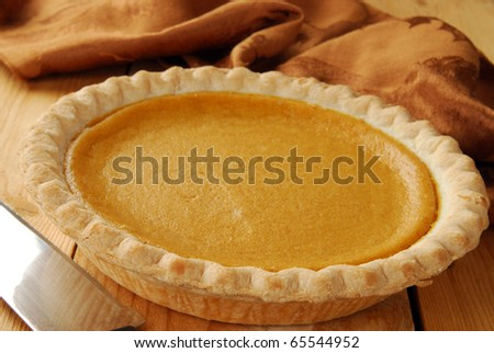 A pumpkin pie on a cutting board with a knife
