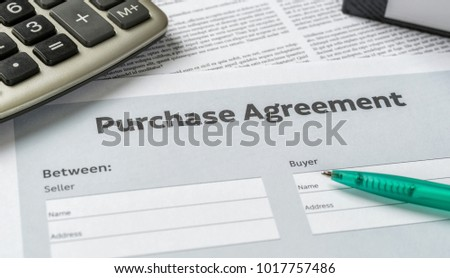 A Purchase agreement with a pen on a desk #1017757486