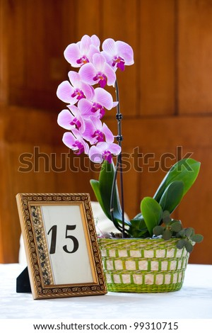 A purple orchid flower centerpiece with a framed table number
