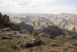 a pyramid made of stones stands against the backdrop of a mountain landscape