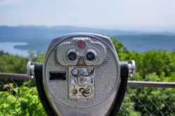 A quarter operated binoculars on top of Prospect mountain overlooking lake george, new york on a sunny day.