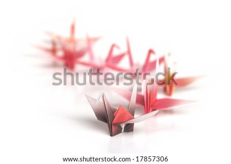 A queue of origami birds on a white background