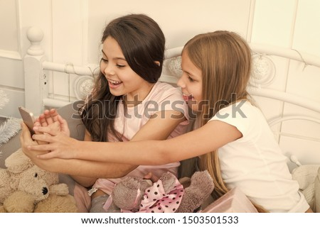 A quick text message to wish a friend a Merry Christmas. Texting Christmas and New Year greetings by phone. Happy small children with mobile phone. Small girls use smartphone in bed. Happy New Year. #1503501533