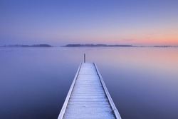 A quiet lake in The Netherlands with a jetty on an early winter morning.