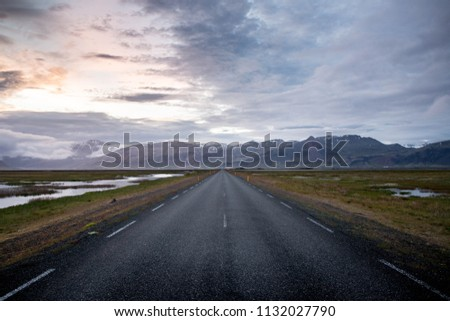 A quiet roadway leads to mountains
