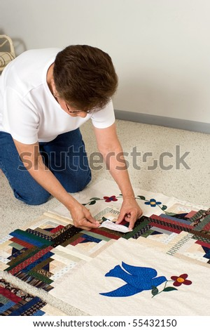 A quilter places a paper label on a panel of fabric prior to quilting. #55432150