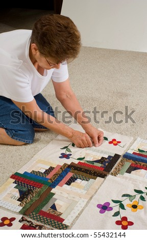 A quilter tags a panel of fabric prior to final assembly of the quilt. #55432144