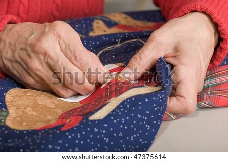 A quilter works on stitching fabric on a quilt.