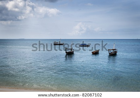 A quintet of traditional fishing wooden dhows moored off the coast of Stonetown, Zanzibar, Tanzania.