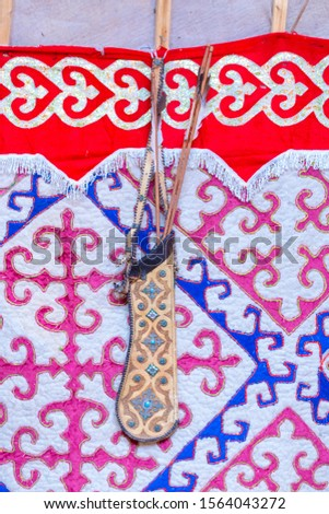 A quiver with arrows hangs on the wall of a yurt, hanged with a felt carpet with an ornament.